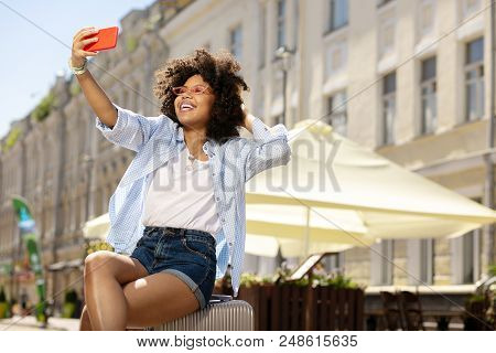 Selfie Break. Adorable Female Tourist Taking A Break And Taking Selfie While Sitting On Her Suitcase