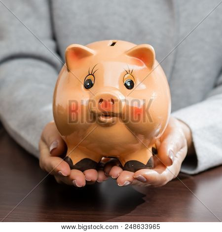Funny Piggy Bank In Woman Hands. Concept Of Future, Business, Saving Money, Economy And Investment