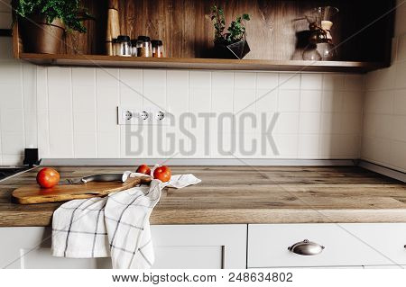 Wooden Board With Knife, Tomatoes On Modern Kitchen Countertop And Shelf With Spices And Plants. Coo