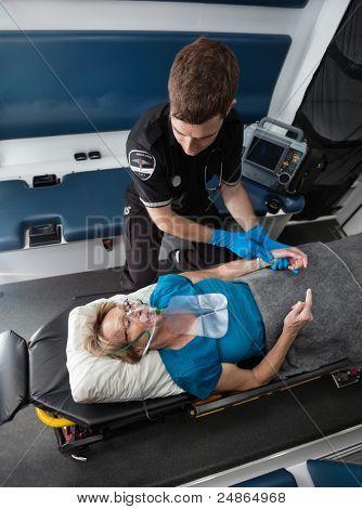 Male ambulance worker taking pulse of elderly senior woman