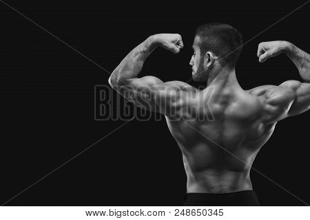 Unrecognizable man bodybuilder shows strong hands and back muscles, athletic trapezius, studio shot on black background, black and white image. poster