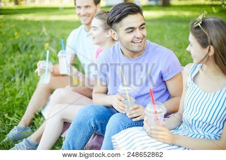 Cheerful teen couple with drinks talking at picnic on summer day with another couple on background