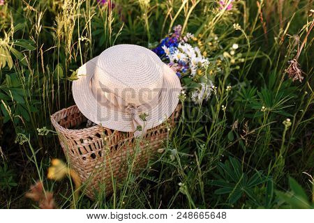 Beautiful Bouquet Of Lupines Lies In A Bag Together With A Straw Hat On The Grass In The Field. Hori