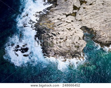 Aerial above stormy sea waves crashing against rock coastline outcrops