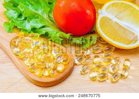 Fish oil, soft capsule, omega 3, supplement food vitamin D capsules with vegetables and fruit greens tomato lemon on wood . still life of healthy food and supplementary  diet concept poster