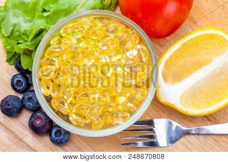 Fish oil, soft capsule, omega 3, supplement food vitamin D capsules with vegetables and fruit greens tomato lemon blueberry on wood . still life of healthy food and supplementary  diet concept poster