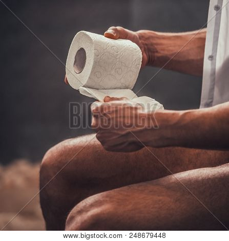 Close Up. Handsome Young Afro American Man Sitting On Toilet With Toilet Paper At Morning. Personal