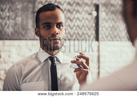 Young Afro American Man In Shirt Applying Perfume And Looking Into Mirror In Bathroom At Morning. Pe