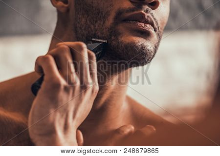 Close Up. Afro American Man Shaving In Bathroom At Morning. Standing Man With Bare Torso In Bathroom
