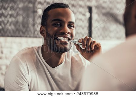 Afro American Man Cleaning Teeth In Bathroom At Morning. Standing Man In T-shirt In Bathroom. Person