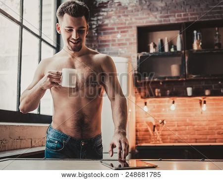 Bare-chested Man With Tablet Pc And Drink Coffee In Kitchen. Man With Bare Torso. Using Portable Dig