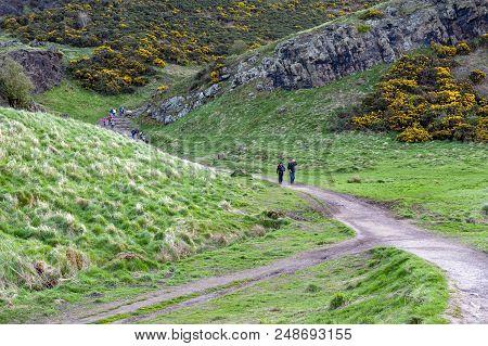 Edinburgh, Scotland - April 2018: Tourist Walking Through Grassy Slopes Of Hills On A Hillwalking Ro