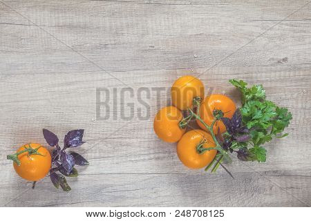 Parsley And Basil Bunch Of Bouquets, Branch Yellow Tomatoes On Light Wooden Surface. Top View, Copy