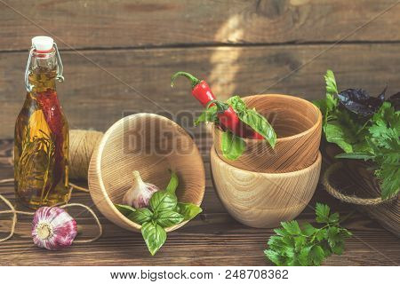 Fresh Delicious Juicy Colorful Red Pepper Chili, Garlic, Parsley, Basil, Oil And Wooden Bowls On Dar
