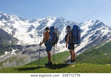Tourists With Hiking Backpacks On The Background Of A Rocky Snow Mountain On A Clear Summer Day. Hik