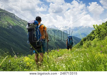 Tourists With Hiking Backpacks In Mountain Hike In Svaneti On Summer Day. Young Guys Go Along The Fo