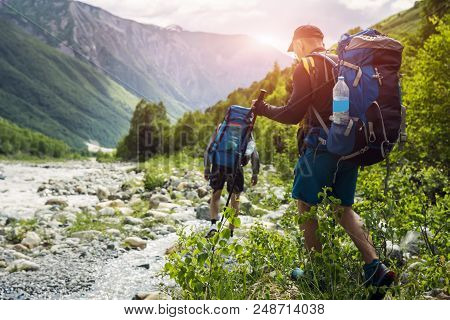 Tourists With Hiking Backpacks On Beautiful Mountain Landscape Background. Climbers Hike To Mounts.