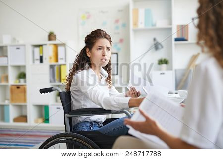 Scowling businesswoman in wheelchair looking at her colleague during discussion of documents at meeting