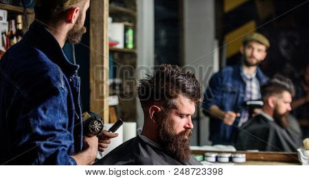 Hipster Lifestyle Concept. Barber With Hairdryer Works On Hairstyle For Bearded Man Barbershop Backg