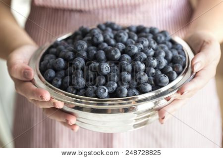 Young woman holding bowl filled blueberries. Crockery with blueberries in woman hands. poster