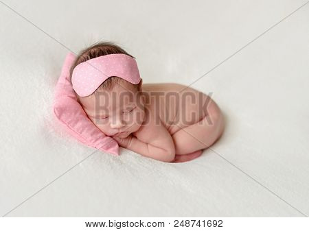 Cute newborn baby girl in a sleep mask