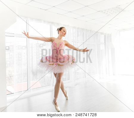 Female ballet dancer in pink tutu in white light room with large windows. Elegant ballerina practicing and smiling