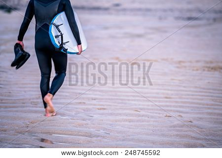 Surfing Instructor Carrying His Shoes And Surfing Board On The Beach In Saint Ives, Cornwall, Uk