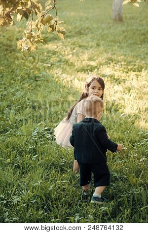 Kids Are Playing. Children, Childhood, Family. Little Boy And Girl Play On Green Grass, Energy. Ener