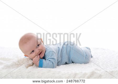 A 2 month old baby boy lying on his stomach on a white blanket. He is  wearing pajamas, has his fingers in his mouth and has a mischievous grin.  Shot in the ...