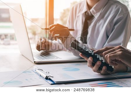 Close Up Businessman Calculate About Budget With Using Calculator And Pointing Laptop On Desk Office