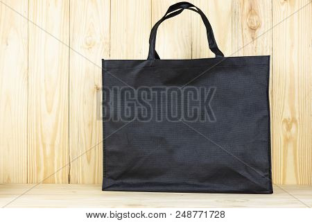 Black Shopping Bag Or Black Bag On Wooden Table.zoom In.