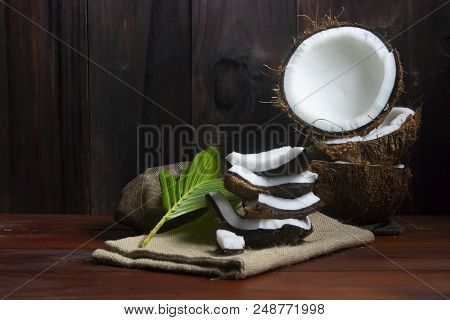 Coconut Half And Coconut Pieces And Leaf  On Wooden Table And Black Wooden Background.1