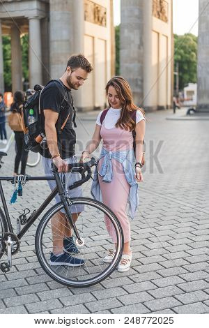 Young Couple Of Travelers With Backpacks And Bicycle At Pariser Platz, Berlin, Germany