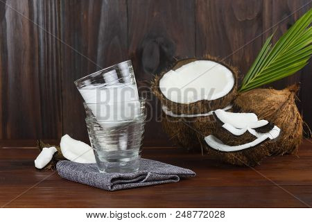Coconut Milk Glass With Coconut Half And Coconut Pieces And Leaf  On Wooden Table.