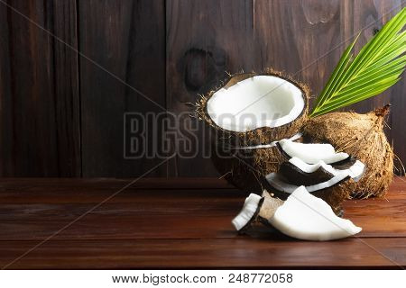 Coconut Pieces With Coconut Half And Leaf  On Wooden Table.