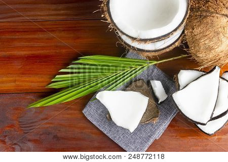 Coconut Topview Such As Coconut Half And Coconut Pieces And Leaf  On Wooden Table.