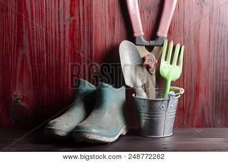 Gardening Equipment Such As Scissors, Spoon, Planting And Repairing. With Boots On Wooden Floor.