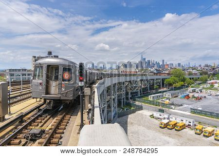 New York, Usa - May 21, 2018: Subway Train Leaving A Station In New York With Skyline In The Backgro