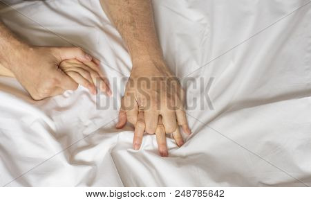 couple hands pulling white sheets in ecstasy, orgasm. Concept of passion. Orgasm. Erotic moments. Intimate concept. Sex couple. Bedroom poster