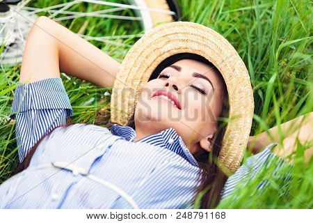 Happy woman lying on a green grass and smiling