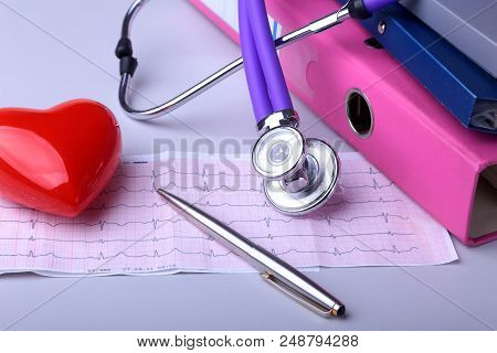 Folder File, Stethoscope, Red Heart And Rx Prescription On The Desk. Blurred Background