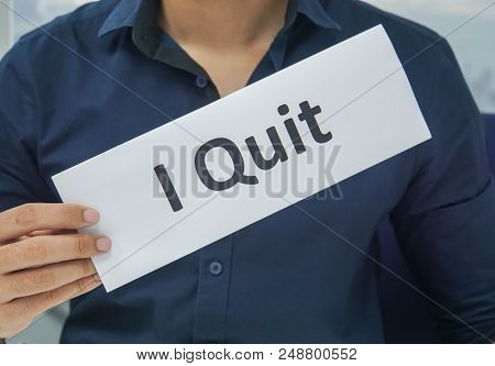 close up businessman hold paper sheet of I quit as resignation letter from the office poster