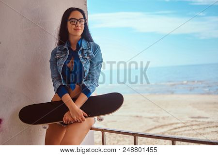 Portrait Of A Sexy Brunette Girl Wearing Short Shorts And Jeans Jacket Holds A Skateboard While Sitt