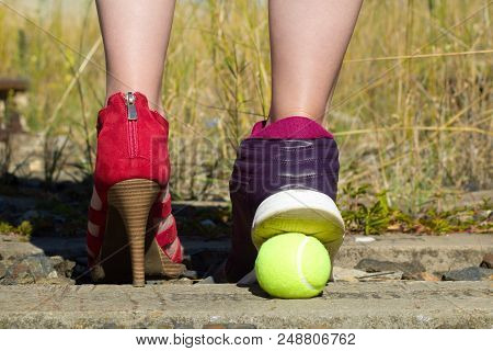 Ladies Legs, One Foot In The Court Shoe And The Other Foot In A Sports Shoe And A Tennis Ball.a Woma