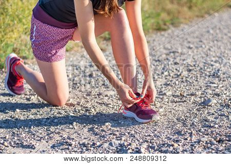 Sport And Fitness. Young Woman Training Outdoor Is Going To Tie Shoelaces.