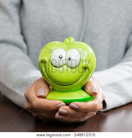 Funny Green Moneybox In Woman Hands. Concept Of Future, Business, Saving Money, Economy And Investme