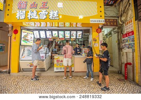 Macua- May 2,2018 :tourists And Shoppers Walking Along A Narrow Street With Colourful Building In Ce