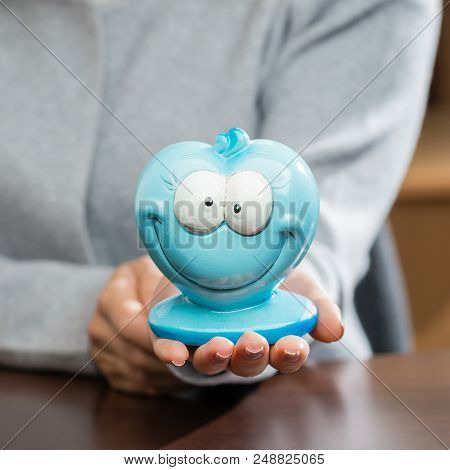 Funny Blue Moneybox In Woman Hands. Concept Of Future, Business, Saving Money, Economy And Investmen