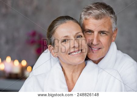 Portrait of mature married couple embracing with bathrobe and looking at camera. Happy senior man and beautiful woman in robes smiling at wellness center. Man and wife relaxing together at day spa.