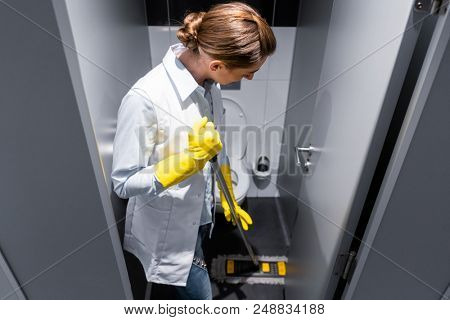 Cleaning lady or janitor mopping the floor in restroom cleaning the stall